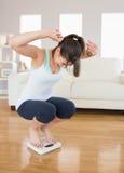 Dysponowany brunetka doping na ważyć waży Zdjęcie Royalty Free