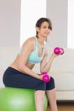 Dysponowany brunetki obsiadanie na ćwiczenie udźwigu ręki balowych ciężarach Zdjęcia Stock