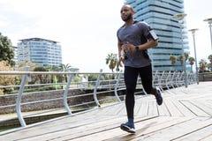 Dysponowany i sporty młodego człowieka bieg w mieście zdjęcie royalty free
