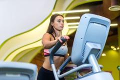 Dysponowany kobiety robić cardio w elliptical trenerze w gym Zdjęcia Royalty Free