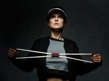 Dysponowany kobiety szkolenie z oporu zespołem przeciw ciemnemu tłu Fotografia Royalty Free