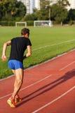 Dysponowany mężczyzna jogging na bieg śladzie przy boiskiem piłkarskim zdjęcie stock