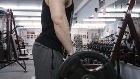 Dysponowany mężczyzna podnosi ciężkiego barbell ciężar zwolnionego tempa wideo zdjęcie wideo