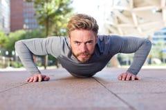 Dysponowany mężczyzna podnosi outdoors robić pcha zdjęcia royalty free