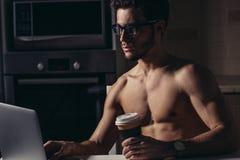 Dysponowany mężczyzna Używa laptopu i napoju kawę przy rankiem zdjęcia stock