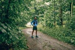 Dysponowany męski jogger dnia szkolenie dla przecinającego kraju śladu lasowej rasy w podeszczowym natura parku obraz stock