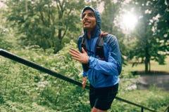 Dysponowany męski jogger dnia szkolenie w deszczu dla przecinającego kraju śladu lasowej rasy w natura parku zdjęcia stock