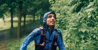Dysponowany męski jogger dnia szkolenie w deszczu dla przecinającego kraju śladu lasowej rasy w natura parku zdjęcie stock