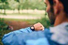 Dysponowany męski jogger dzień używać smartwatch podczas przecinającego kraju śladu lasowej rasy w natura parku Zdjęcia Royalty Free