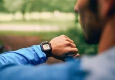 Dysponowany męski jogger dzień używać smartwatch podczas przecinającego kraju śladu lasowej rasy w natura parku Zdjęcie Royalty Free
