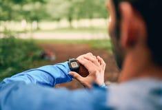 Dysponowany męski jogger dzień używać smartwatch podczas przecinającego kraju śladu lasowej rasy w natura parku Obraz Stock