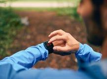 Dysponowany męski jogger dzień używać smartwatch podczas przecinającego kraju śladu lasowej rasy w natura parku Zdjęcie Stock