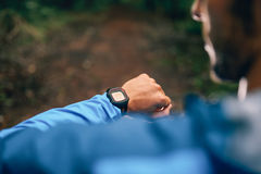 Dysponowany męski jogger dzień używać smartwatch podczas przecinającego kraju śladu lasowej rasy w natura parku zdjęcia stock