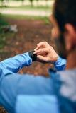 Dysponowany męski jogger dzień używać smartwatch podczas przecinającego kraju śladu lasowej rasy w natura parku Fotografia Royalty Free