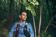 Dysponowany męski jogger odpoczywa podczas dnia szkolenia dla przecinającego kraju śladu lasowej rasy w natura parku fotografia stock