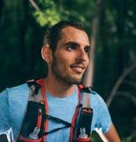Dysponowany męski jogger odpoczywa podczas dnia szkolenia dla przecinającego kraju śladu lasowej rasy w natura parku obraz royalty free