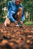 Dysponowany męski jogger wiąże buty podczas gdy dnia szkolenie dla przecinającego kraju śladu lasowej rasy w natura parku fotografia stock