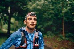 Dysponowany męski jogger z headlamp odpoczywa podczas szkolenia dla przecinającego kraju śladu rasy w natura parku obrazy stock