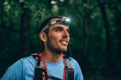 Dysponowany męski jogger z headlamp odpoczywa podczas szkolenia dla przecinającego kraju śladu rasy w natura parku Fotografia Royalty Free