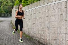 Dysponowany młody żeński jogger jogging na chodniczku w podmiejskim terenie Ładna dziewczyna pracująca out outdoors zdjęcie royalty free