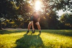Dysponowany młody człowiek ćwiczy z kettlebell outdoors Zdjęcie Royalty Free
