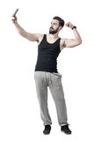 Dysponowany młody człowiek napina bicep ręki mięsień podczas gdy brać selfie fotografię z telefonem komórkowym Zdjęcie Stock