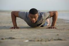 Dysponowany młody człowiek podnosi outdoors robić pcha Zdjęcie Royalty Free