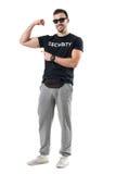 Dysponowany młody człowiek w sportswear z cipy paczką pokazuje napinający bicep ręki mięsień Obraz Stock