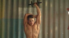 Dysponowany mięśniowy mężczyzna używa jego dumbbell pracować jego zbiory
