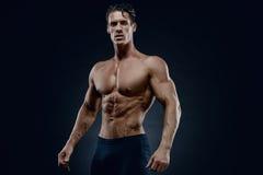 Dysponowany samiec model pozuje jego mięśnie Zdjęcie Royalty Free