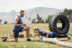Dysponowany spełniania pushup ćwiczenie podczas gdy mężczyzna pomiarowy czas Zdjęcia Stock