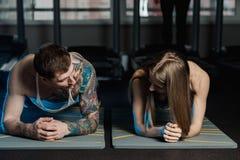 Dysponowany sportive mężczyzna i kobieta robi deski sedna ćwiczenia szkoleniu popieramy mięśnia pojęcia gym sporta sportowa spraw obrazy royalty free