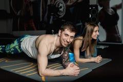Dysponowany sportive mężczyzna i kobieta robi deski sedna ćwiczenia szkoleniu popieramy mięśnia pojęcia gym sporta sportowa spraw fotografia stock