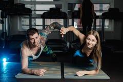Dysponowany sportive mężczyzna i kobieta robi deski sedna ćwiczenia szkoleniu popieramy mięśnia pojęcia gym sporta sportowa spraw fotografia royalty free