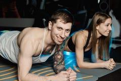 Dysponowany sportive mężczyzna i kobieta robi deski sedna ćwiczenia szkoleniu popieramy mięśnia pojęcia gym sporta sportowa spraw zdjęcia stock