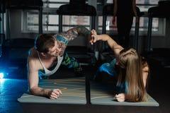 Dysponowany sportive mężczyzna i kobieta robi deski sedna ćwiczenia szkoleniu popieramy mięśnia pojęcia gym sporta sportowa spraw obraz royalty free