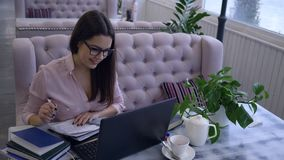 Dystansowy uczenie, uśmiechnięta młoda kobieta pisze notatkach w notatnika obsiadaniu przy stołem z laptopem w kawiarni zbiory wideo