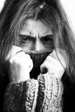 Dyster kvinna för ung brunett i tröja över hela hennes framsida, rört till hår Arkivbilder