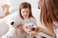 Dyster liten flicka som tar preventivpillerar Arkivfoto