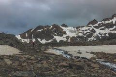 dyster sky En ensam turist går upp kullen längs floden Royaltyfria Bilder