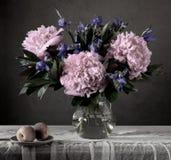 Dyster stilleben med blommor och frukt i en mörkertangent royaltyfri bild