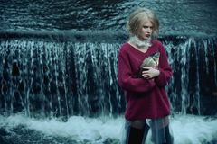 Dystopian fashion portrait of model with dead fish in river of sewage against waterfall of dirty and polluted water Royalty Free Stock Images