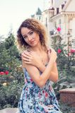 Dystyngowana młoda kobieta w błękitnym smokingowym obsiadaniu przeciw starym budynkom i ogródowi różanemu Spojrzenie kieruje kame obraz stock
