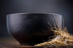 Dystyngowany czarny ceramiczny puchar i wysuszeni ucho na drewnianym tle zdjęcia royalty free