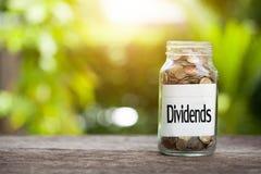Dywidendy formułują z monetą w szklanym słoju z Savings i pieniężny zdjęcie stock