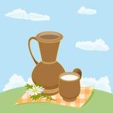 Dzbanek i filiżanka mleko na łące Zdjęcie Stock