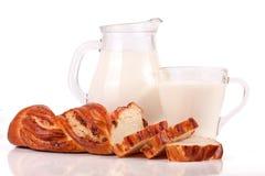 Dzbanek i szkło mleko z bochenkiem odizolowywającym na białym tle chleb Fotografia Stock