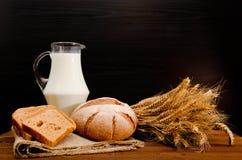 Dzbanek mleko, round żyto chleb, snop banatka i chlebów plasterki na parciaku, Zdjęcie Royalty Free