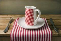 Dzbanek na biel talerzu na drewnianym stole. Obrazy Royalty Free