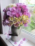 Dzbanek z kwiatami przy okno Fotografia Royalty Free